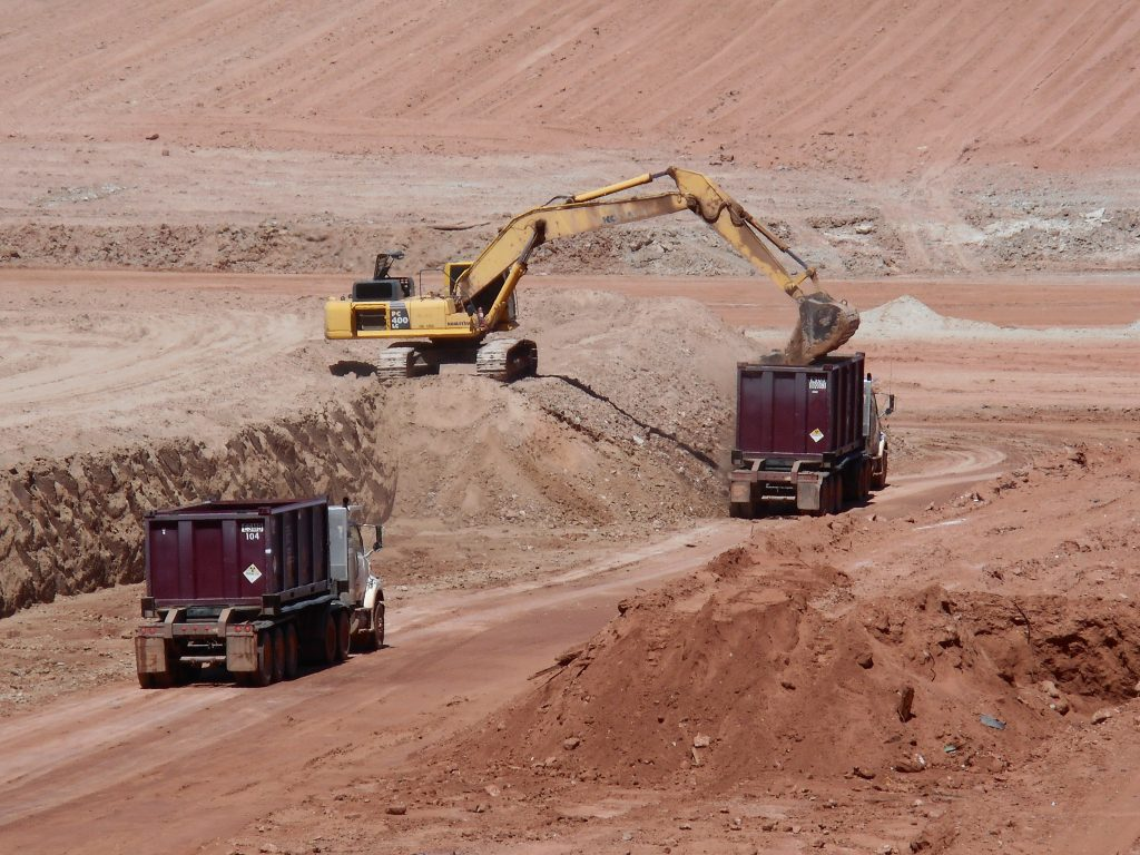 Moab UMTRA Project equipment operators load mill tailings into containers. Haul truck drivers then lid and rinse the containers and load them onto a train. Each train carries up to 144 containers to the Crescent Junction, Utah disposal cell.